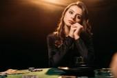 krásná zamyšlená žena koukal u pokerového stolu v kasinu