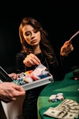 beautiful woman taking euro banknotes from box at table in casino