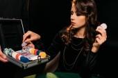 Fotografia ragazza attraente che cattura fiches da poker dalla scatola al tavolo in casinò