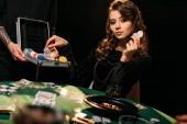 Fotografia ragazza attraente prendere poker chip dalla scatola al tavolo nel casinò, distogliendo lo sguardo