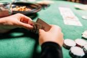 Fotografia immagine potata della ragazza che tiene le carte da poker al tavolo in casinò