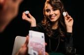 Fotografia attraente ragazza sorridente che tiene fiches da poker e guardando uomo al tavolo da poker casinò