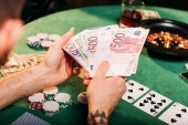 cropped image of tattooed man holding euro banknotes at poker table in casino