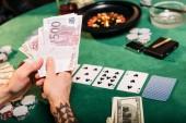Oříznout obrázek Tetovaný muž držení hotovosti u pokerového stolu v kasinu