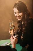 atraktivní dívky cinkání sklenic šampaňského u pokerového stolu v kasinu