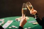Fotografia immagine potata di donne clinking con bicchieri di champagne al tavolo da poker casinò