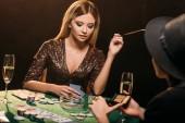 atraktivní dívky kouření cigaret a hrát poker v kasinu u stolu