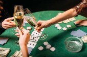 cropped image of girls clinking with glasses of champagne at poker table in casino