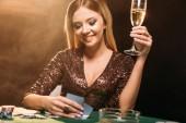 s úsměvem atraktivní dívka hospodářství sklenku šampaňského a při pohledu na poker karty u stolu v kasinu