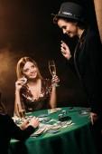 s úsměvem atraktivní dívky s brýlemi šampaňského mluví u pokerového stolu v kasinu