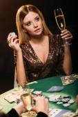 atraktivní dívka hospodářství sklenici šampaňského a poker čip u stolu v kasinu