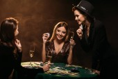attractive smiling girls looking at each other at poker table in casino