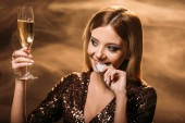 Fotografie smiling attractive girl holding glass of champagne and biting poker chip on brown