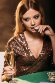 Fotografie attractive girl holding glass of champagne and biting poker chip at table in casino
