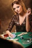 atraktivní dívka hrát poker a při pohledu na krupiér v kasinu