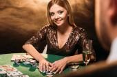 Selektivní fokus usmívající se atraktivní dívka s poker žetony a při pohledu na krupiér v kasinu