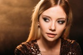 Fotografie portrait of attractive girl with makeup in sparkling party dress looking away on brown