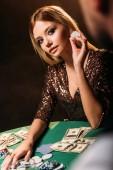 Fotografia ragazza attraente che tiene chip poker e guardando il croupier al casinò