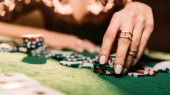 oříznutý obraz dívky, hrát poker a žetonů u stolu v kasinu