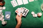 oříznutý obraz dívky, hrát poker v kasinu u stolu a držení hrací karty