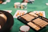 Fotografie ruleta a doutníky a poker karty na stole v kasinu