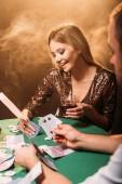 Fotografia sorridente ragazza attraente giocando a poker con croupier al casinò, le banconote in euro che cade sul tavolo