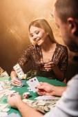 Fotografia bella ragazza felice giocando a poker con croupier al casinò, le banconote del dollaro che cadono sul tavolo