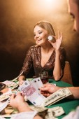 Happy atraktivní dívka hrát poker s krupiér a drží poker chip Casino