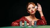 atraktivní dívka v červené lesklé šaty opřený o stůl, pořádání pokerových žetonů a při pohledu od izolovaný na černém pozadí