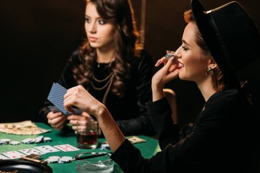 attractive smiling girls playing poker at table in casino