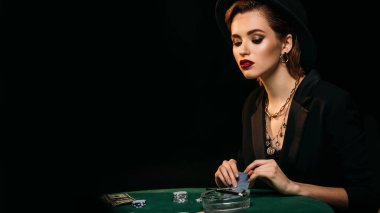 attractive girl looking down at poker table in casino