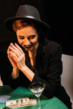 attractive smiling girl in hat sitting at poker table in casino, dollar banknotes and cocktail on tabletop
