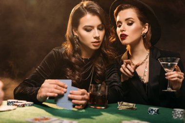 attractive girls playing poker at table in casino, woman pointing on something to friend