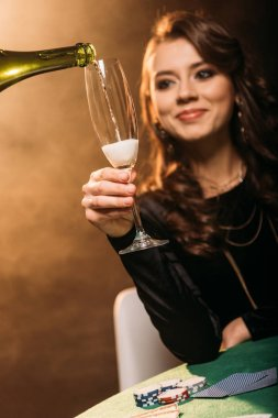 waiter pouring champagne in glass for attractive cheerful girl at poker table in casino