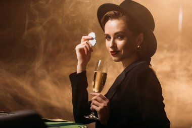 attractive girl in jacket and hat holding glass of champagne and poker chips at table in casino