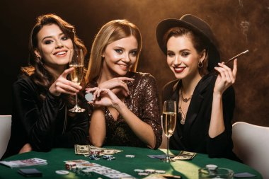 attractive girls with glass of champagne, cigarette and poker chips sitting at table in casino and looking at camera