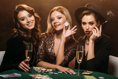 smiling attractive girls sitting at table in casino and looking at camera