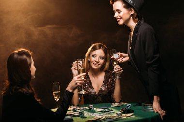 happy beautiful women with glasses of champagne talking at poker table in casino