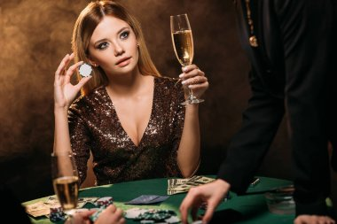 beautiful woman holding glass of champagne and poker chip at table in casino