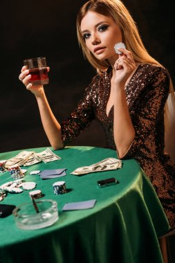 attractive smiling girl holding glass of whiskey and poker chip at table in casino, looking at camera