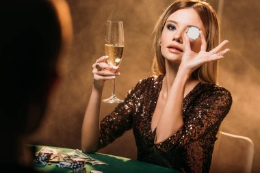 attractive girl holding glass of champagne and covering eye with poker chip at table in casino