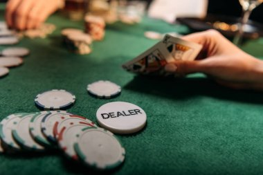 cropped image of girl playing poker at table in casino, dealer chip on tabletop