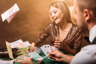 happy attractive girl playing poker with croupier at casino, euro banknotes falling on table
