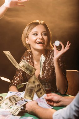 excited attractive girl holding poker chip with croupier at casino, dollar banknotes falling on table