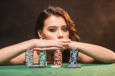 beautiful brown haired girl leaning on poker chips and looking at camera isolated on black