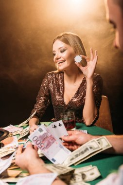 happy attractive girl playing poker with croupier and holding poker chip at casino