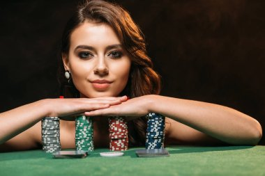 attractive brown haired girl leaning on poker chips and looking at camera isolated on black