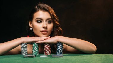 beautiful brown haired girl leaning on poker chips and looking away isolated on black