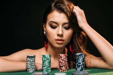 beautiful brown haired girl leaning on table and looking at poker chips isolated on black