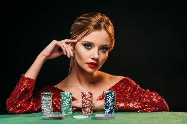 attractive girl in red shiny dress leaning on table with poker chips and looking at camera isolated on black
